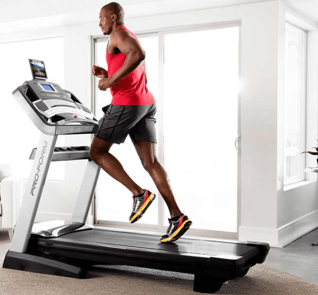 Man in red tank top and black shorts running in a Proform Pro 2000 treadmill