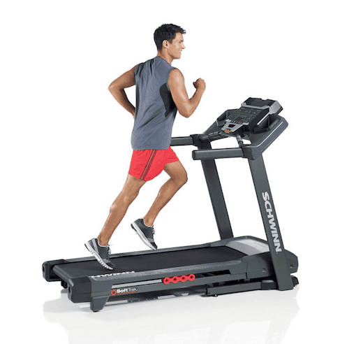 Man wearing gray sleeveless shirt and red pants running in a Schwinn 830 Treadmill