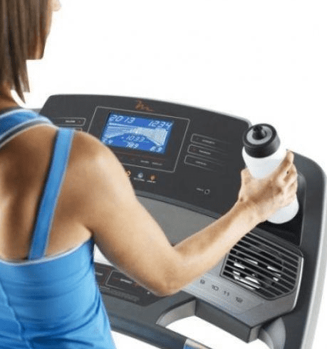 Woman wearing a blue top and putting a white water container on the Freemotion Treadmill's dashboard