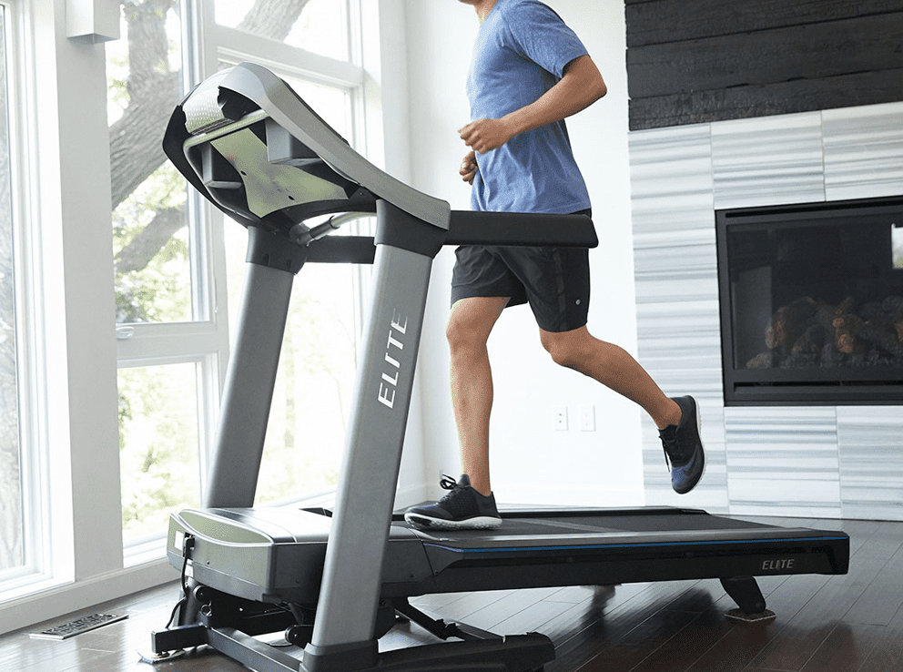 Man in sky blue shirts and black shorts running in a treadmill inside his house