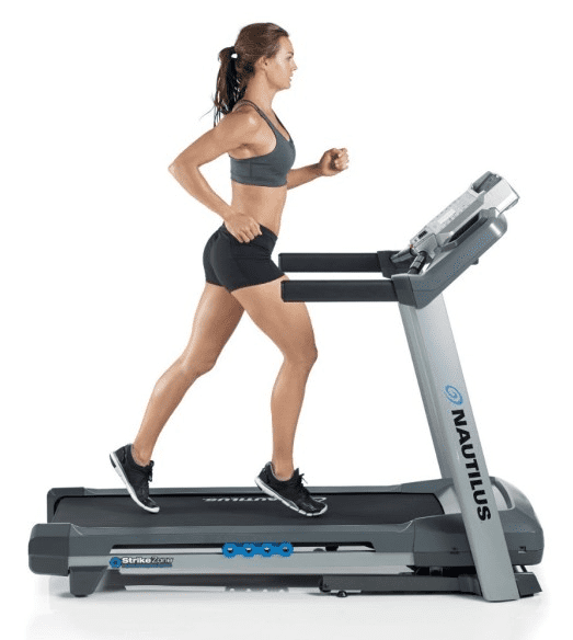 Woman in gray sports bra and black shorts running in a Nautilus T614 Treadmill