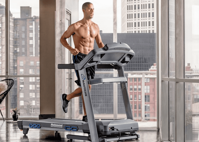 Shirtless man in black shorts running in a treadmill