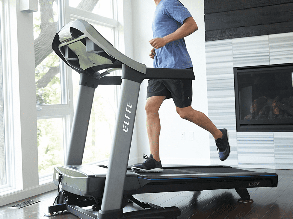 Man wearing blue shirt and black short while running in a Horizon Elite T9-02 Treadmill for Home