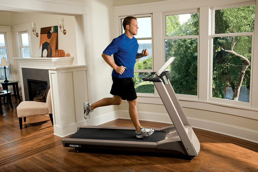 Man in blue shirts and black shorts running in a treadmill inside his house