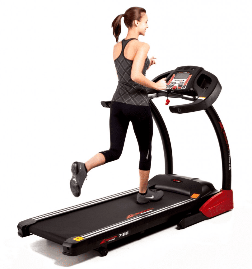 Woman in a gray top and black leggings running in a treadmill with red design