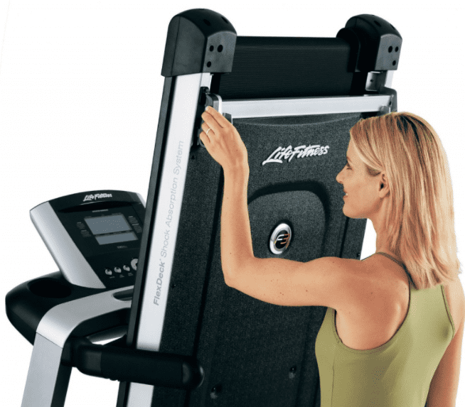 Woman wearing a green top and touching the edge of a life fitness treadmill