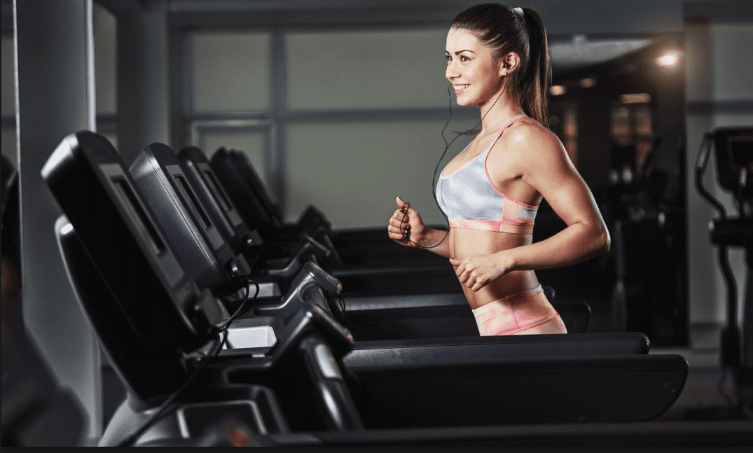 Smiling woman in sports bra running in a treadmill