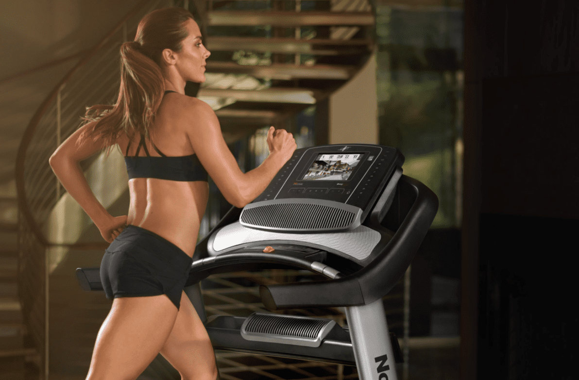 Woman in black sports bra and shorts running in a jillian treadmill