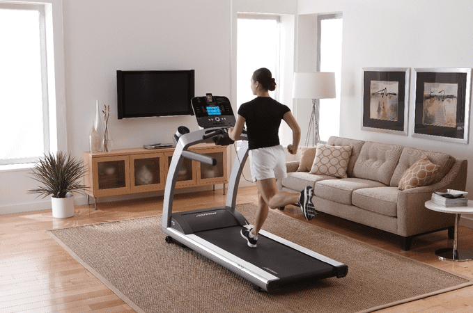 Woman in black top wearing a shorts and running on a treadmill inside a room