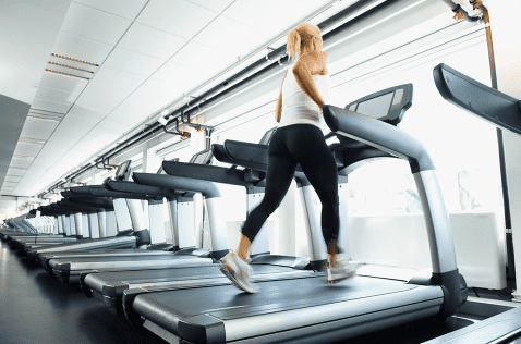 Woman wearing a white top and black leggings and running on a treadmill near a lot of treadmills