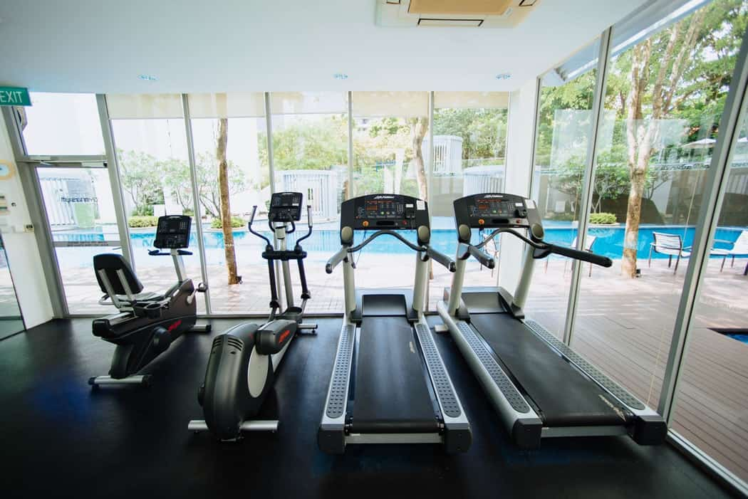 black treadmills and elliptical trainers in glass room